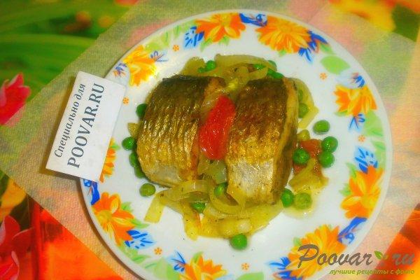 Жареная сельдь на сковороде с овощами Изображение